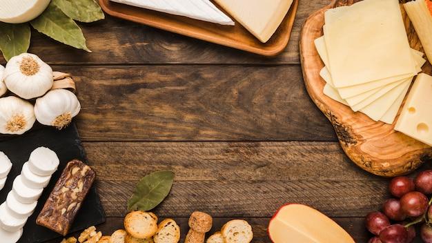 Köstlicher käse mit brotscheibe und roten trauben auf rustikaler tabelle