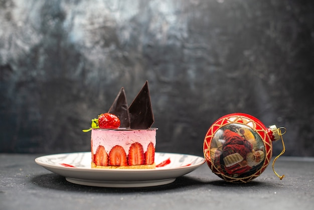 Köstlicher käsekuchen der vorderansicht mit erdbeere und schokolade auf ovalem teller und rotem weihnachtsballspielzeug auf dunklem