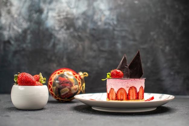 Köstlicher käsekuchen der vorderansicht mit erdbeere und schokolade auf ovaler tellerschüssel mit erdbeeren
