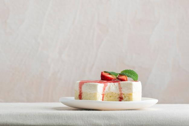 Köstlicher käsekuchen mit frischen erdbeeren und minze auf weißem teller. seitenansicht.