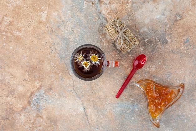Köstlicher kamillentee mit erdnusskrokant und marmelade