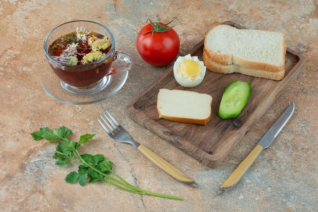Köstlicher kamillentee mit tomate und brot.
