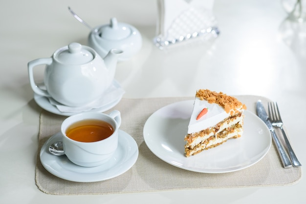 Köstlicher karottenkuchen und eine tasse schwarzen tee auf dem tisch in einem gemütlichen café