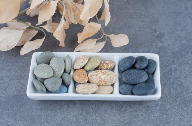 Köstlicher keks im tablett neben den blättern auf dem marmorhintergrund.