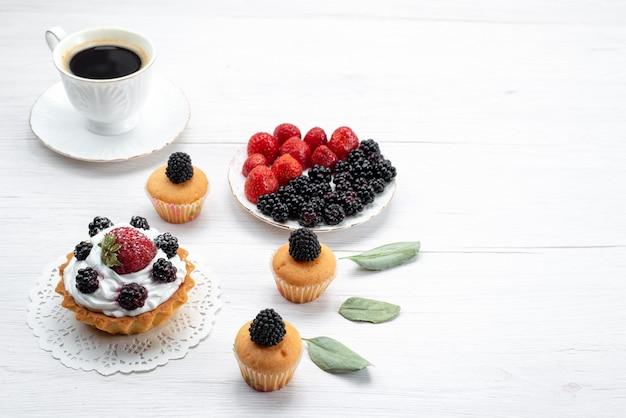 Köstlicher kleiner kuchen mit sahne und beerenplätzchen und beeren innerhalb platte auf weißem schreibtisch, kuchenkeks backen fruchtbeere