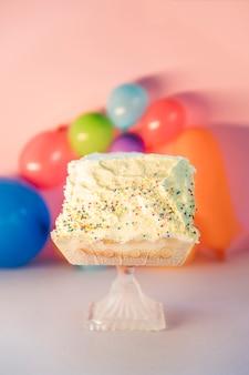 Köstlicher kuchen auf kristallcakestand gegen bunte ballone