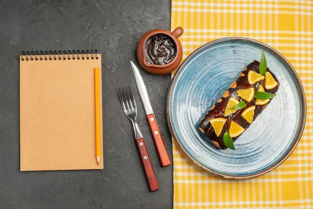 Köstlicher kuchen, dekoriert mit orange und schokolade, serviert mit gabel und messer und notizbuch