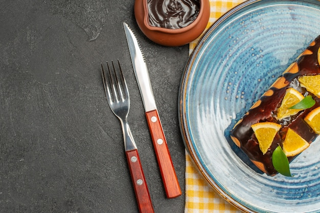 Köstlicher kuchen, dekoriert mit orange und schokolade, serviert mit gabel und messer