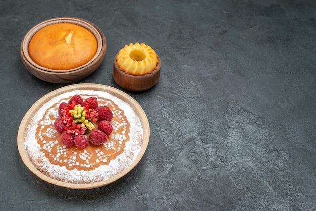 Köstlicher kuchen der vorderansicht mit zuckerpulver und himbeeren auf grauem hintergrund kuchentorte fruchtbeere süßes plätzchen Kostenlose Fotos