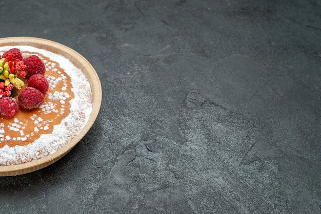 Köstlicher kuchen der vorderansicht mit zuckerpulver und himbeeren auf grauem hintergrund tortenkuchen fruchtbeere süßes plätzchen