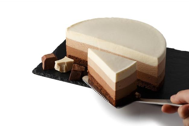 Köstlicher kuchen mit drei verschiedenen arten schokolade auf platte des schiefers. isoliert. cook nimmt ein stück kuchen auf einen teigspatel.