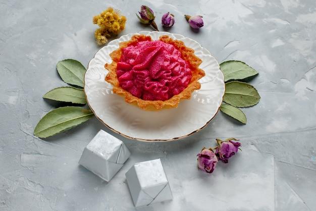 Köstlicher kuchen mit rosa sahne und pralinen auf hellem schreibtisch, kuchenkeks süße backcreme