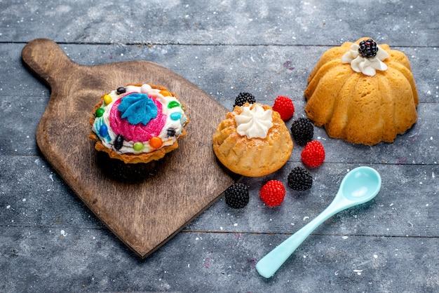 Köstlicher kuchen mit sahne und süßigkeiten zusammen mit beerenplätzchenkuchen auf hellem schreibtisch, kuchenkeks süßes backbonbon