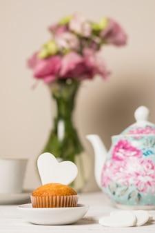 Köstlicher kuchen nahe blumen und teekanne