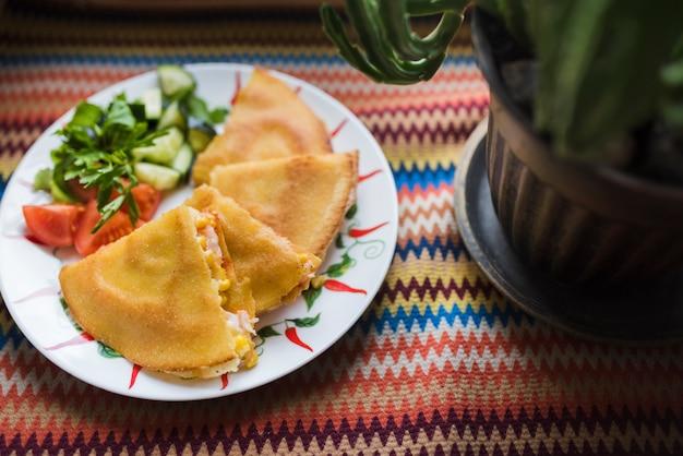 Köstlicher kuchen nahe gemüsesalat auf platte nahe blumentopf