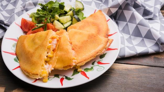 Köstlicher kuchen nahe gemüsesalat auf platte