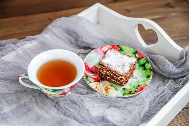 Köstlicher kuchen und eine tasse heißer tee auf einem weißen tellersegment.