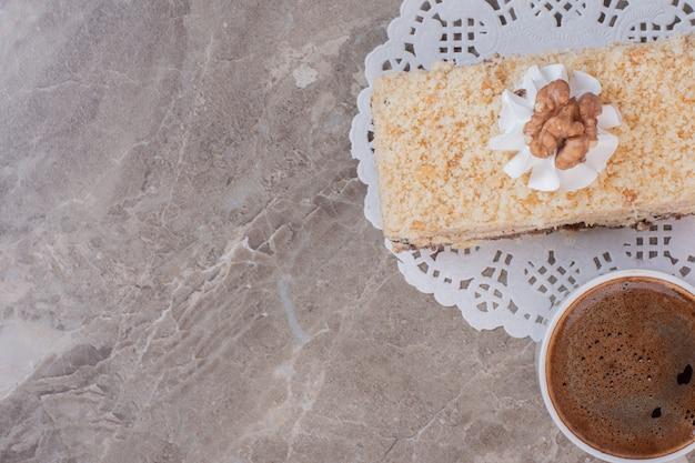 Köstlicher kuchen und eine tasse kaffee auf marmoroberfläche.