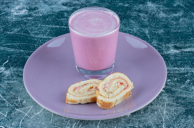 Köstlicher kuchen und erdbeermilchshake auf dem teller, auf dem blauen hintergrund. hochwertiges foto