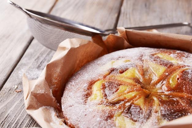 Köstlicher kuchen und sieb mit puderzucker auf holztisch