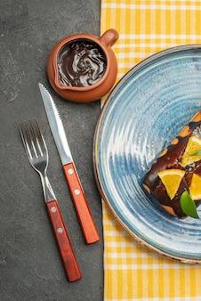 Köstlicher kuchen, verziert mit orang und schokolade, serviert mit vertikaler ansicht von gabel und messer