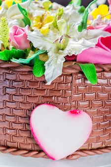 Köstlicher kuchenkorb mit verschiedenen blumen und dekorativem herzen