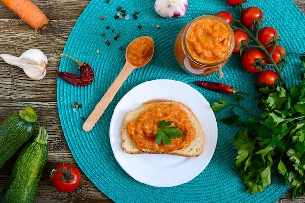 Köstlicher kürbiskaviar in einem glas und auf weißbrotscheiben auf dem tisch verteilen. hausgemachter kaviar mit zucchini, knoblauch, karotten, tomatensauce. vegane küche. die draufsicht. flach liegen