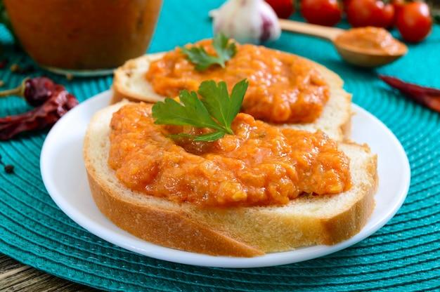 Köstlicher kürbiskaviar in einem glas und auf weißbrotscheiben auf dem tisch verteilen. hausgemachter kaviar mit zucchini, knoblauch, karotten, tomatensauce. vegane küche. nahansicht