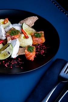 Köstlicher lachs mit pastete und hummus im restaurant. gesundes exklusives essen auf großer schwarzer platte nahaufnahme