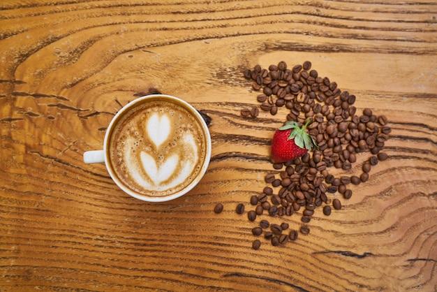 Köstlicher lattekaffee und rote erdbeere