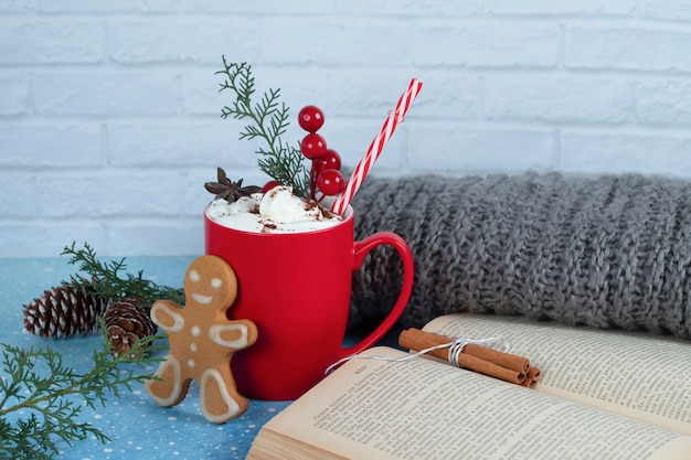 Köstlicher lebkuchenplätzchen, buch und rote tasse kaffee auf blau