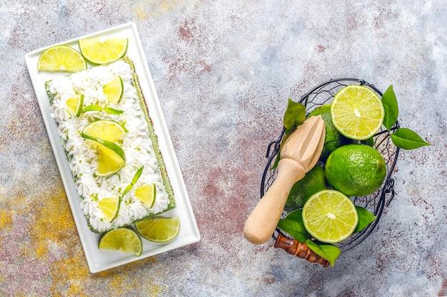 Köstlicher limettenkuchen mit frischen limettenscheiben und limetten.