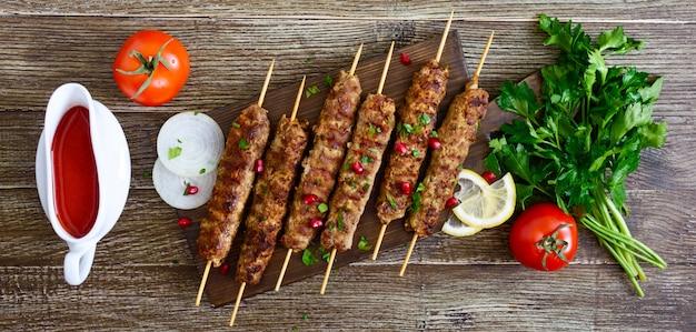 Köstlicher lula-kebab auf einem holztisch. gehacktes fleisch auf holzspießen, gegrillt. banner