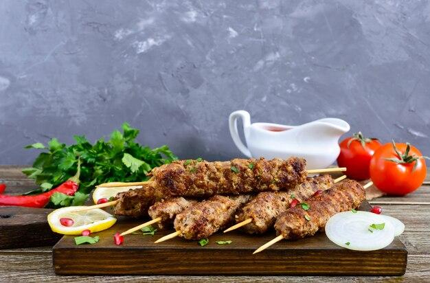 Köstlicher lula-kebab auf einem holztisch. gehacktes fleisch auf holzspießen, gegrillt. östliche küche.