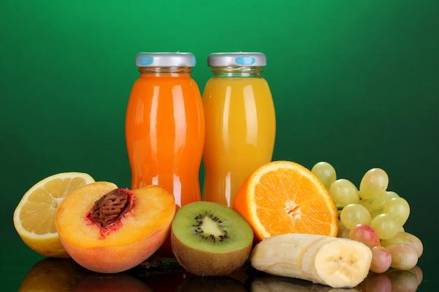 Köstlicher mehrfruchtsaft in einer flasche und frucht daneben auf grünem hintergrund