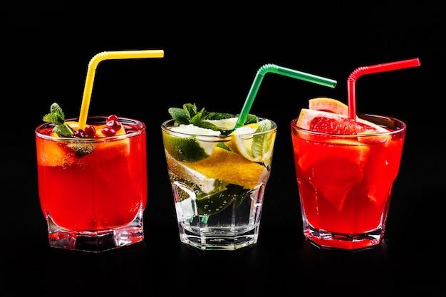 Köstlicher mojito, rum und cola, blutorange und wodka-cocktails, serviert mit früchten