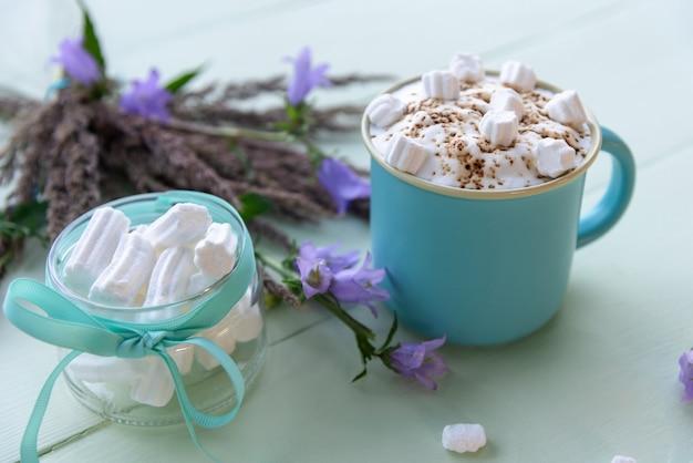 Köstlicher mokka mit weißen marshmallows auf einem azurblauen raum mit lila blumen.