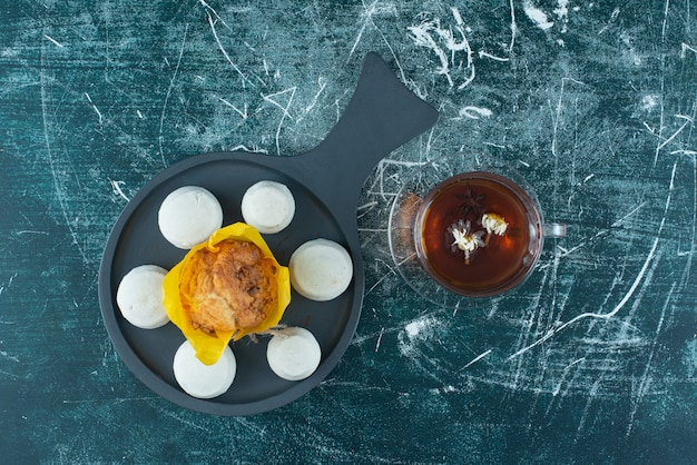 Köstlicher muffin mit einer tasse kräutertee. foto in hoher qualität