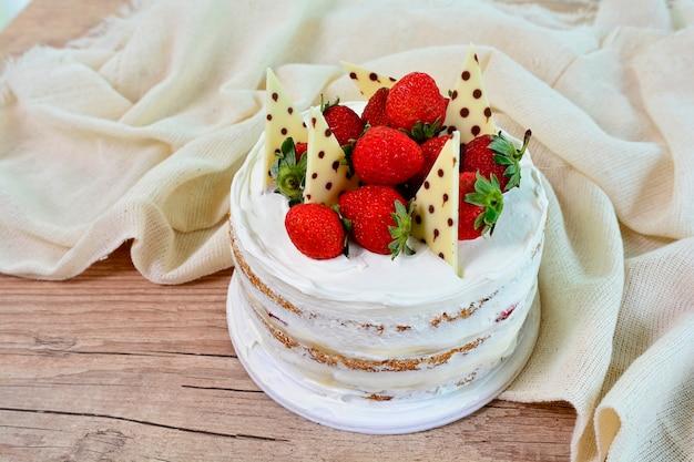 Köstlicher nackter kuchen mit erdbeeren und schokoladenstücken auf belag, süßspeise