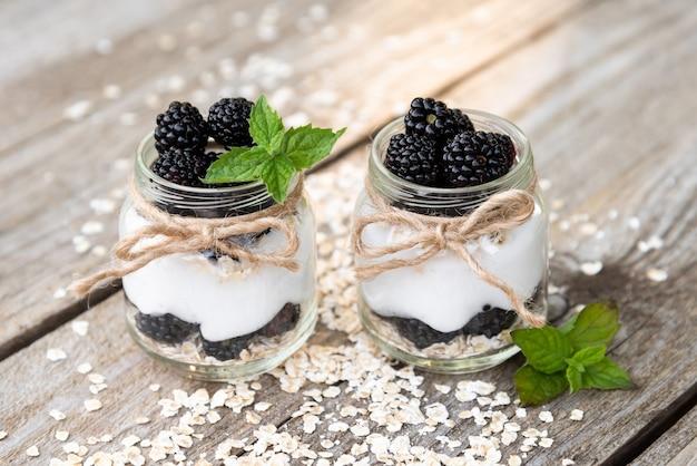 Köstlicher naturjoghurt mit brombeeren, himbeeren und minzblättern. in gläsern.