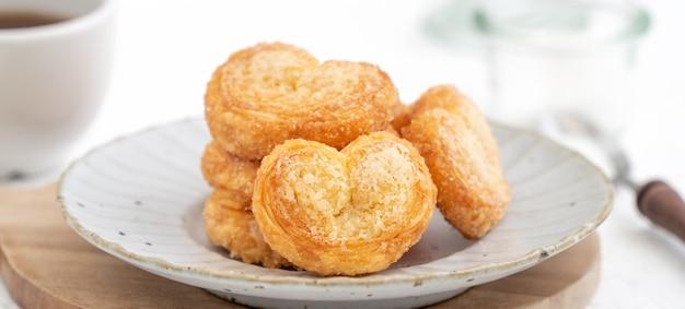 Köstlicher palmier-schmetterling-blätterteigkeks in herzform für das dessertkonzept zum muttertag.
