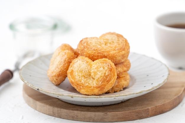 Köstlicher palmier-schmetterlings-blätterteigplätzchen in herzform für valentinstag-dessertkonzept.