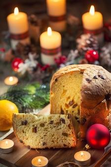 Köstlicher panettone auf weihnachtstisch mit dekorationen und adventskranz und kerzen.