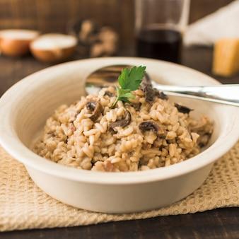 Köstlicher pilz risotto in der weißen schüssel mit löffel