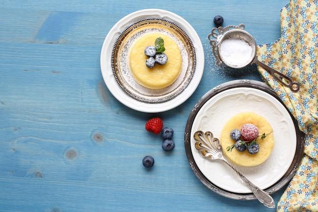 Köstlicher puddingkuchen der zitrone diente mit beeren auf platte