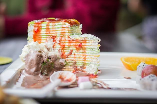 Köstlicher regenbogenkuchen der kucheneiscreme, spuren essend