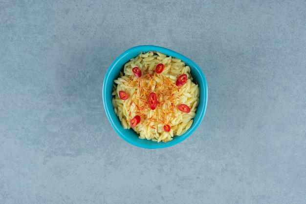 Köstlicher reis mit tomatenscheiben in blauer schüssel.