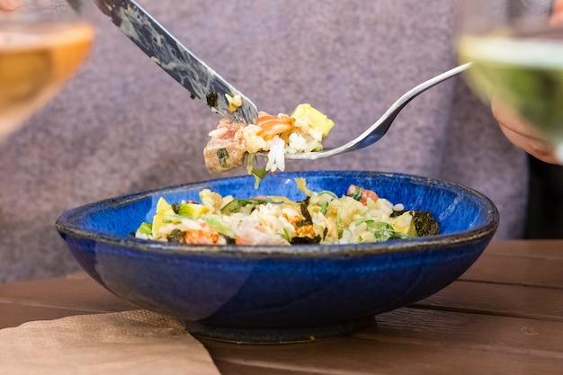 Köstlicher reissalat mit gemüse und roten fischstücken auf einer gabel. speicherplatz kopieren