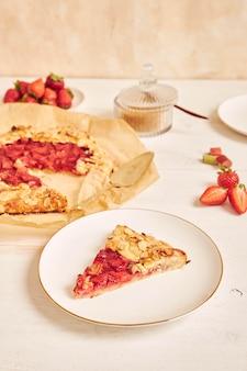 Köstlicher rhabarber-erdbeer-gallat-kuchen mit zutaten auf einem weißen tisch