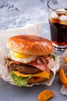 Köstlicher rindfleischburger mit gebratenem speck und eiern, käse, tomaten und kopfsalat. fastfood
